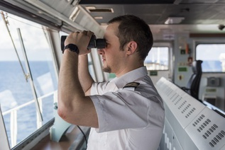 Captain with binoculars on ship's bridge